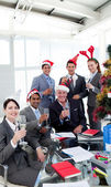 Business with novelty Christmas hat toasting at a party — Stock Photo
