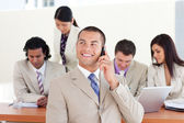 Attractive manager on phone in front of his team — Stock Photo