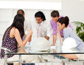 International architect co-workers reviewing blueprints — Stock Photo