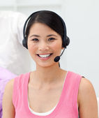 Charming young businesswoman talking on headset — Stock Photo
