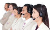 Positive business team with headset on standing in a row — Stock Photo