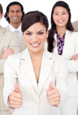 Attractive businesswoman and her team with thumbs up — Stock Photo
