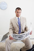 Confident manager reading a newspaper — Stock Photo