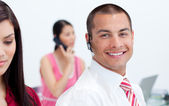 Portrait of a man with an hands-free set and his team — Stock Photo