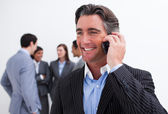 Attractive manager on phone with his team in the background — Stock Photo