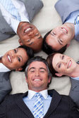 Smiling business team lying on the floor with heads together — Stock Photo