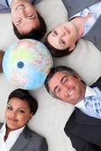 Multi-ethnic business team lying on the floor around a terrestri — Stock Photo