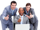 Business with thumbs up looking at a laptop — Foto de Stock