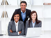 Enthusiastic businesswomen and their colleague working at a lapt — Stock Photo