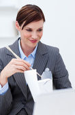 Businesswoman eating chinese food with chopstick — Stock Photo