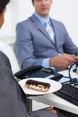 Close-up of a businesswoman carrying a pastry to her desk — Stock Photo