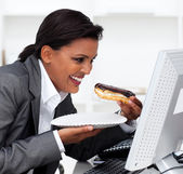Close-up of a laughing businesswoman eating a chocolate eclair — Stock Photo