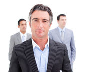 Charming businessman posing in front of his team — Stockfoto