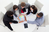 Internatonal Business team holding a terrestrial globe — Stockfoto