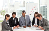Multi-ethnic business team sitting around a conference table — Stockfoto