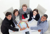 High angle of a diverse business team holding a terrestrial glob — Stock Photo