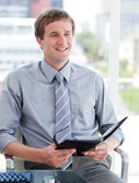 Charming male executive looking at his agenda — Stock Photo