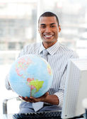 Ethnic businessman holding a terrestrial globe — Stock Photo