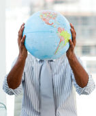 Afro-american businessman holding a terrestrial globe — Stock Photo