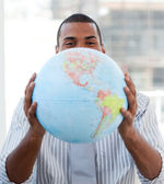 Fortunate businessman holding a terrestrial globe — Stock Photo