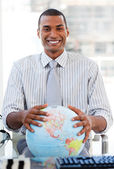 Enthusiastic businessman showing a terrestrial globe — Стоковое фото