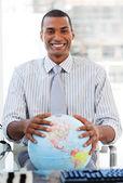 Homme d'affaires enthousiaste montrant un globe terrestre — Photo