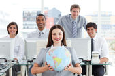 Pretty businesswoman and her team showing a terrestrial globe — Stock Photo