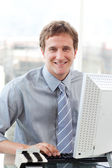 Smiling businessman working at a computer — Stock Photo