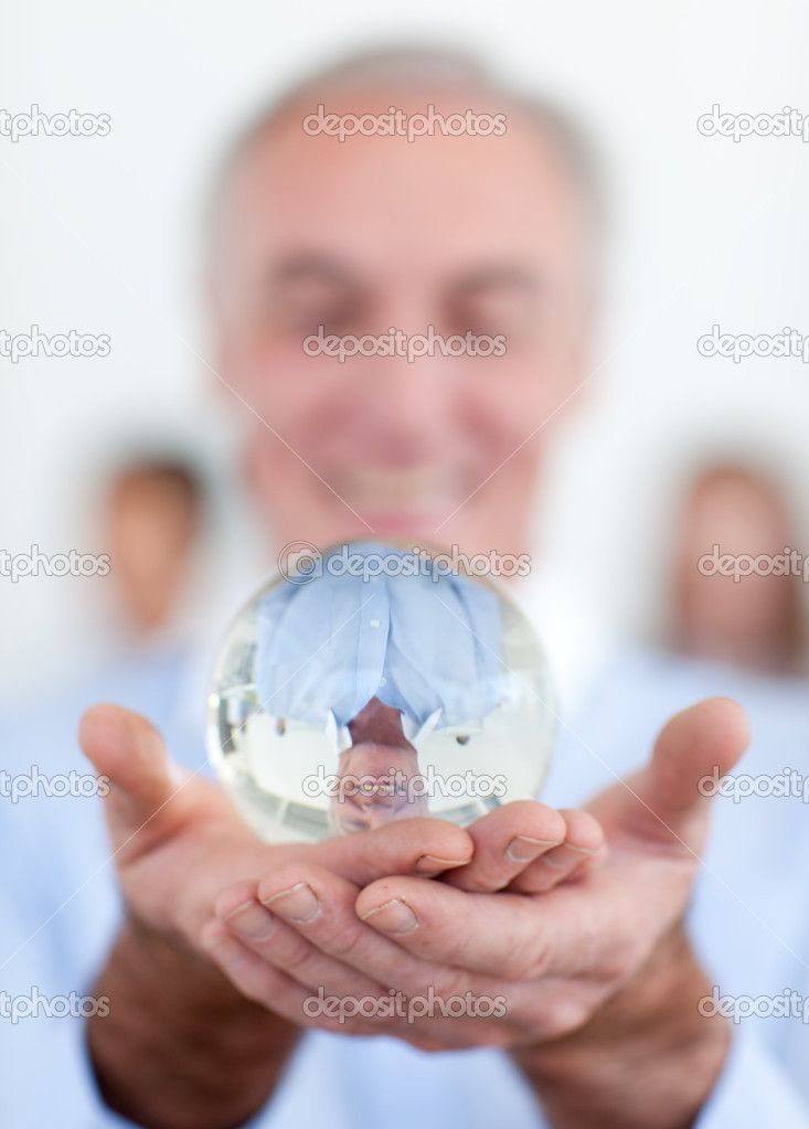 Senior businessman holding a crystal ball at work  Stock Photo #10280918
