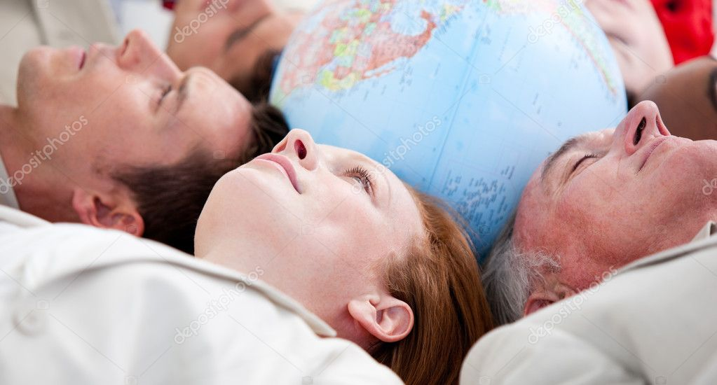 Serious business lying on the floor around a terrestrial globe — Stock Photo #10281415