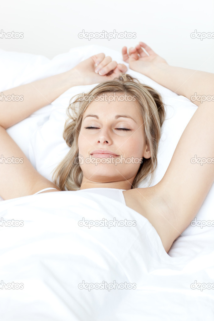 Relaxed woman sleeping on a bed against a white background — Stock Photo #10282635