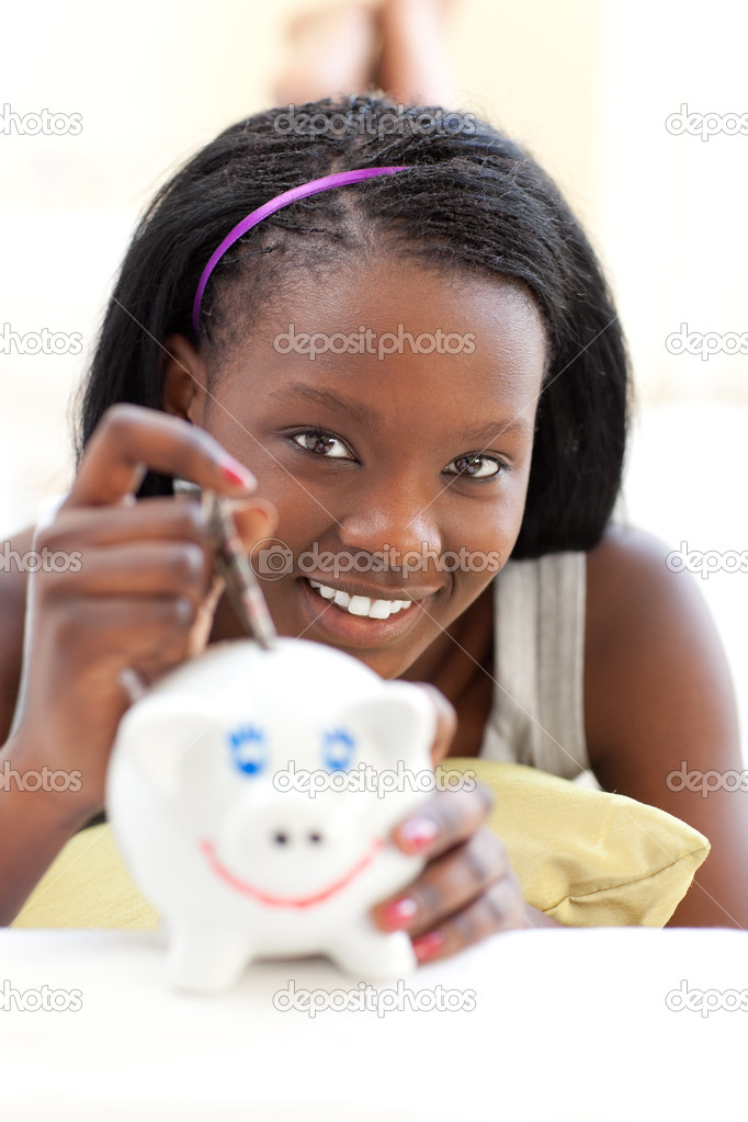 Jolly teen girl putting money in a piggy-bank against a white background — Stock Photo #10283002