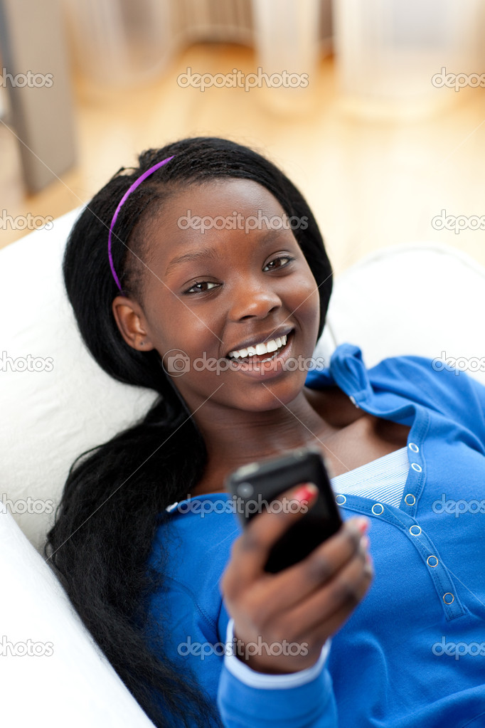 Jolly woman sending a text lying on a sofa in the living-room — Stock Photo #10283471