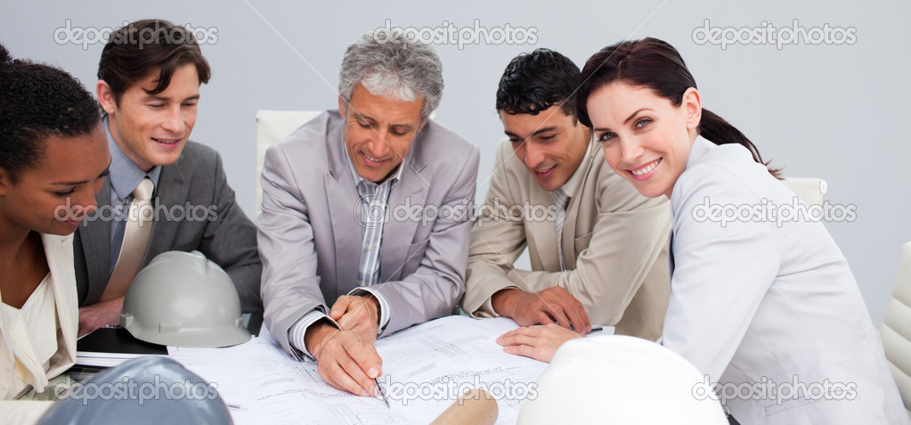 Beautiful female architect studying plans with her colleagues in a meeting — Stock Photo #10286538