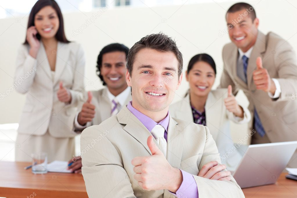 Successful manager in front of his team with thumbs up in the office — Stock Photo #10288208