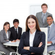 Charismatic female executive sitting in front of her team — Stock Photo #10290011