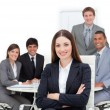 Charismatic female executive sitting in front of her team — Stock Photo