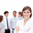 Confident manager in front of her team with folded arms — Stock Photo #10290071