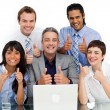 Smiling business group with thumbs up — Stock Photo