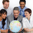Smiling business looking at a terrestrial globe — Stock Photo
