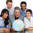 Foto Stock: Business group showing diversity looking at terrestrial glob