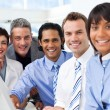 Multi-ethnic smiling business team sitting in a row — Stock Photo #10290139