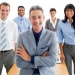 Smiling manager with folded arms in front of his team — Stock Photo