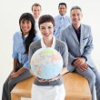 Cheerful multi-ethnic business holding a terrestrial glob — Stock Photo