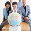 Smiling business team holding a terrestrial globe - Foto de Stock