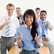 Lucky co-workers with thumbs up - Stock Photo