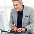 Positive businessman working at a computer — Stock Photo