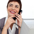 Radiant Businesswoman on phone at her desk — Stock Photo #10290356