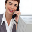 Assertive Businesswoman on phone at her desk — Stock Photo #10290357