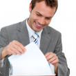 Smiling young businessman studying a document - Stock Photo